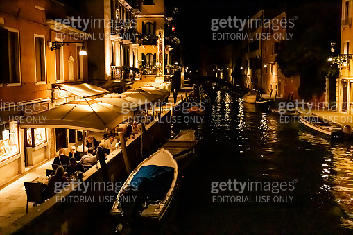 Venice, Italy - September 9, 2019: tourists sitting near outdoor cafe with view at canal at night in Venice, Italy