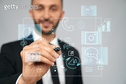 Businessman writing business plan on virtual projection.