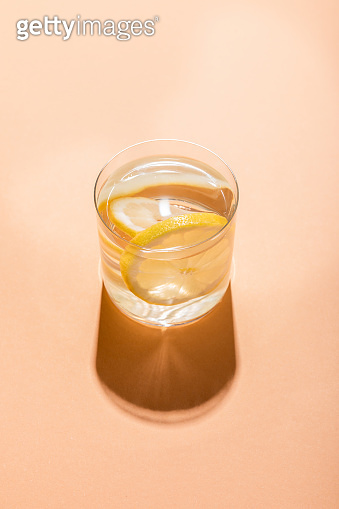 glass of fresh water with lemon slices on beige with shadow