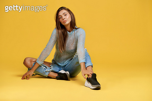 Attractive stylish girl sitting on floor