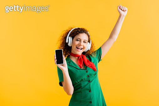 cheerful woman in wireless headphones holding smartphone with blank screen isolated on yellow