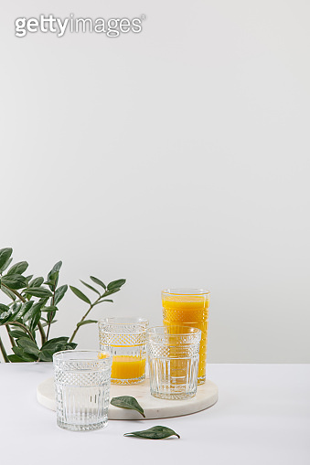 glasses of delicious yellow smoothie on white surface near green plant isolated on grey