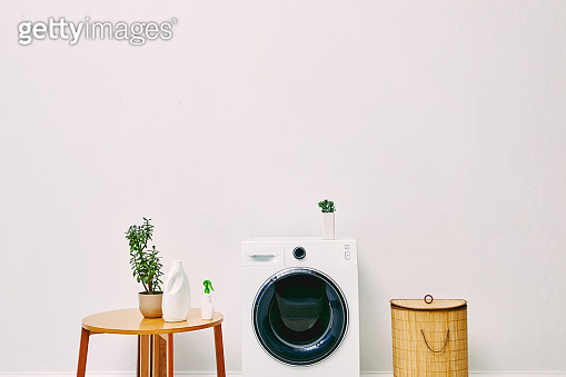 green plants and bottles near wooden coffee table, laundry basket and modern washing machine in bathroom