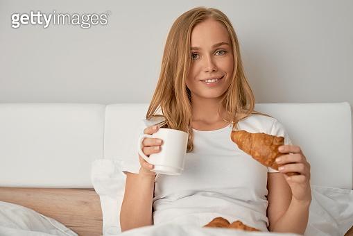 Girl enjoying breakfast in bed.