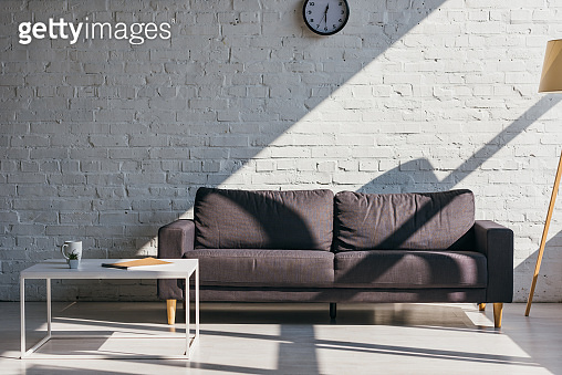 living room with grey sofa and table with cup of coffee, notepad and succulent in sunlight
