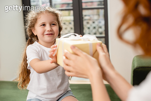 selective focus of cute daughter giving present to mother