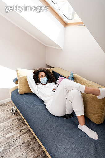 african american woman in medical mask lying on sofa and reading magazine