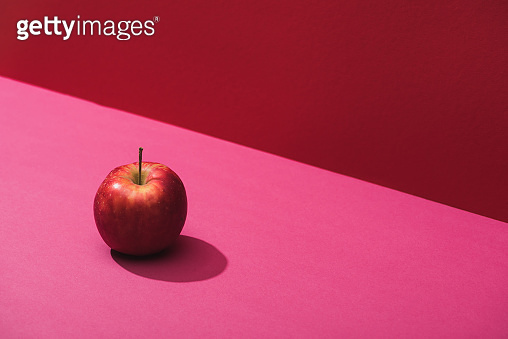 fresh juicy apple on red and pink background