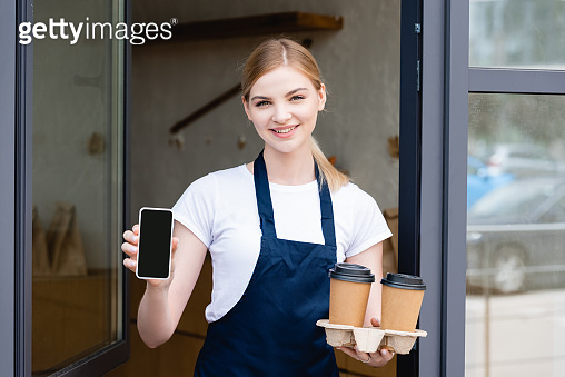 Front view of beautiful waitress holding smartphone and paper cups near window of cafe
