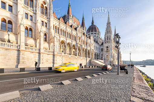Hungarian parliament building front and a taxi passing on the riverbank on a sunny day in autumn season.