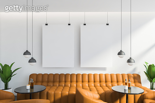 Orange sofa and posters in white cafe interior