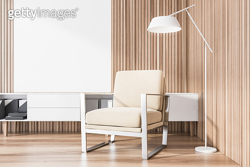 Wooden lounge area with beige armchair and poster