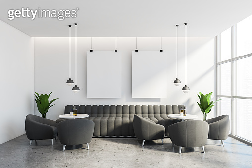 White cafe interior with grey sofa and posters