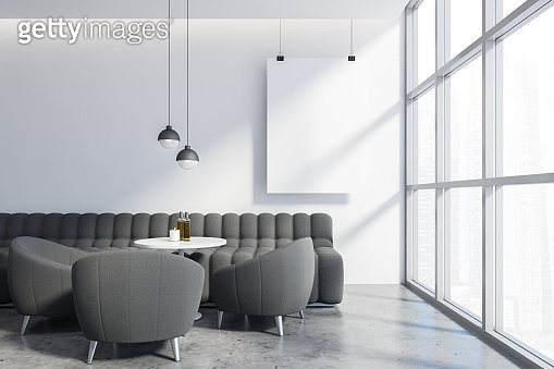Grey sofa and armchairs in white cafe with poster