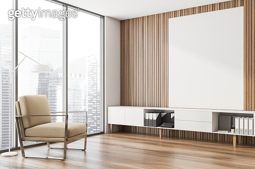 Wooden lounge corner, beige armchair and poster