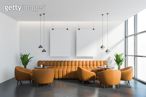 White cafe interior with orange sofa and posters