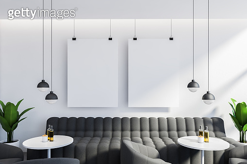 Grey sofa and posters in white cafe interior
