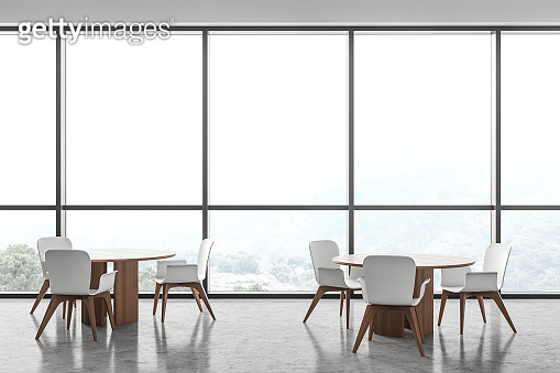 Round tables in panoramic white cafe