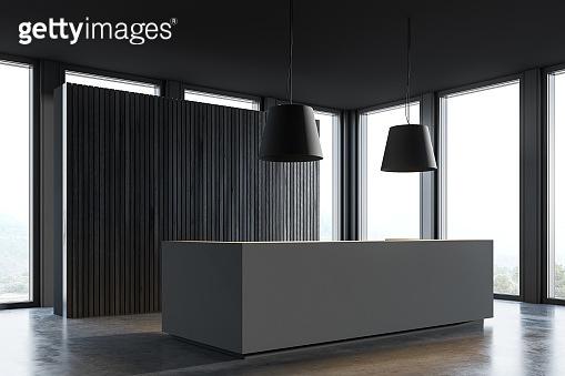 Gray reception desk in dark wooden office corner