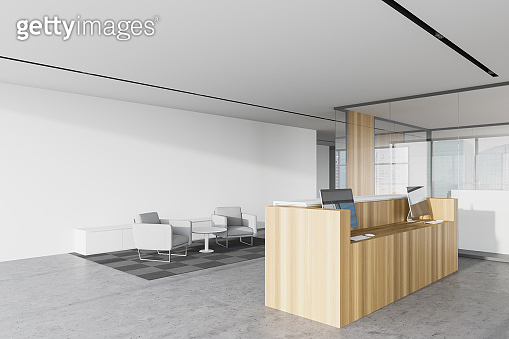 Wooden reception and lounge in white office