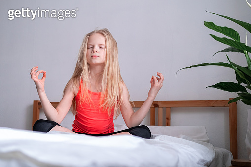 Little Blonde girl is engaged in meditation and yoga, exercise at home, sitting lotus position on bed. Relaxation