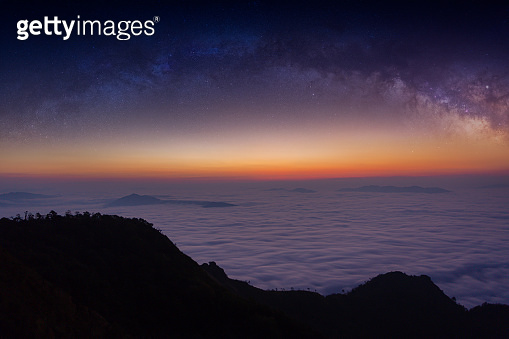 The silhouette of misty mountains and milky way