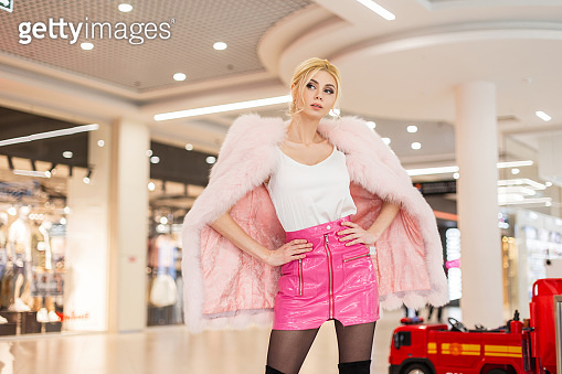 Fashion model young beautiful woman in luxurious pink fur coat in leather glamorous fashionable skirt with stylish hairstyle posing in modern mall. Elegant chic blonde girl travels in store.