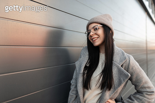 Pretty happy young hipster woman with cute smile in glasses in sweater in knitted fashionable hat in gray trendy coat in the city. Fashion portrait positive girl model in fashionable clothes outdoors.