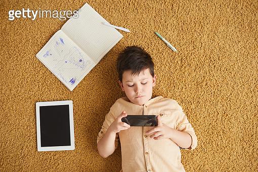 Modern Child Using Gadgets on Floor