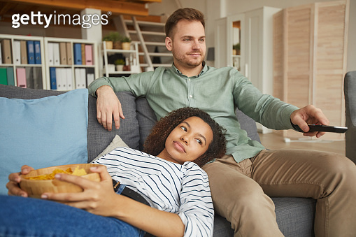 Young Couple Relaxing on Sofa by TV