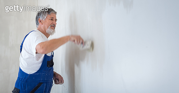 Senior man painting a room of rental appartment