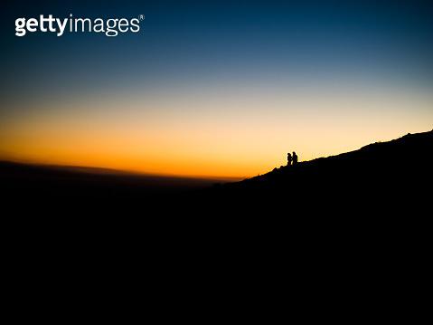 Couple silhouetted against the dusk sky