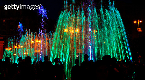 Multi-colored neon lights illuminate the jets of a powerful urban singing fountain in the late evening.