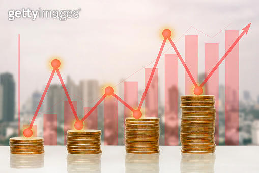 Money coin stack with growing graph and arrow up on building blur background.
