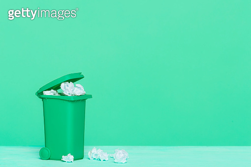 A green plastic garbage bin and paper on green background, great for recycling concepts and designs.