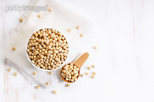 Closeup soy beans in ceramic bowl on white wooden table