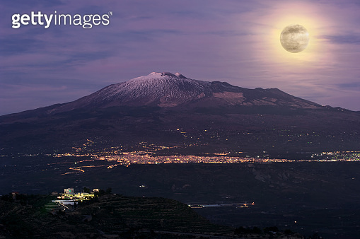 night landscape with full moon on city and Etna Volcano in Sicily natural landmark