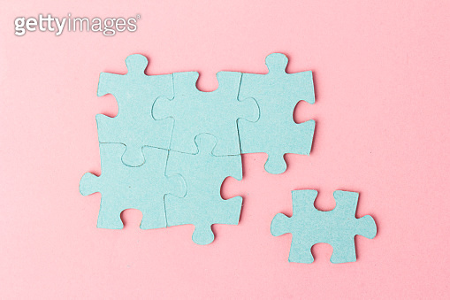 Blue puzzle pieces with empty space for your text and design on pink background.