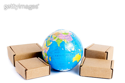 Earth globe is surrounded by boxes isolated on white background. Global business and international transportation of goods products. Shipping freight, world trade and economics. Distribution, import export. Commodity turnover