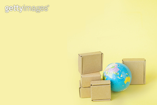 Earth globe is surrounded by boxes. Global business and international transportation of goods products. Shipping freight, world trade and economics. Distribution, import export. Commodity turnover