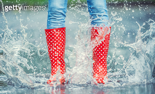 Detail of a moment when red polka dot rain boots jumped into a puddle of water, splashing all around.