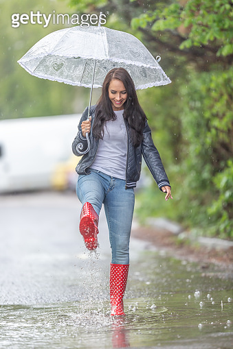 Woman with an umbrella walking in rainboots in a puddle under a heavy rain.