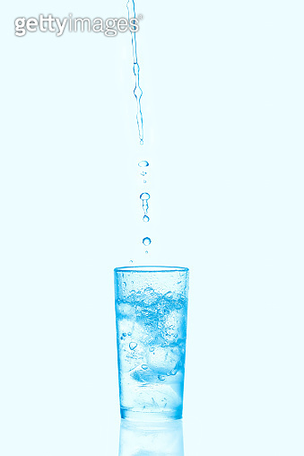 Pouring water into glass with ice isolated on blue background.