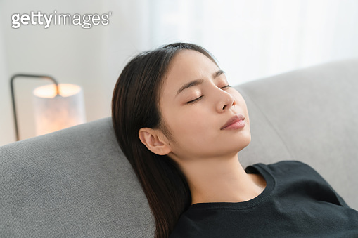 Asian woman resting comfortably and relaxing on a sofa after work at home.