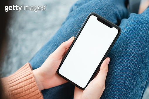 Hand holding smartphone mockup of blank screen. Take your screen to put on advertising.