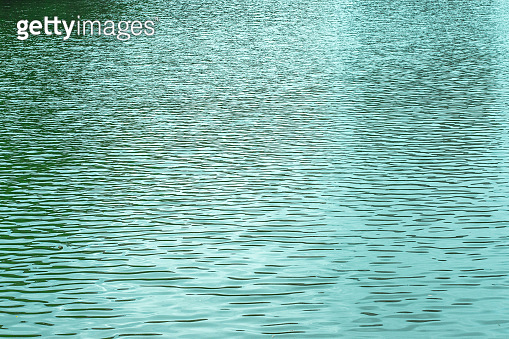 Blue texture of the surface of the water pond lake river, small waves on the water surface, light breeze. Textured ripple effect on the water. Backdrop natural background for design
