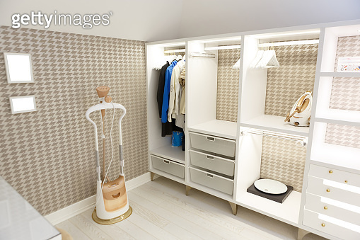 Beige wardrobe for clothes in the dressing room.