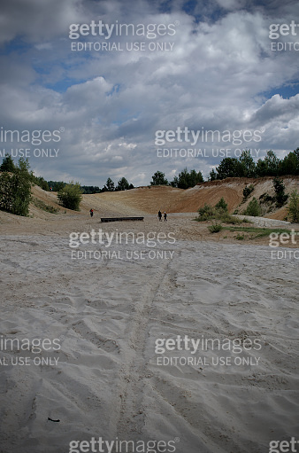 Few people are walking and riding on the bottom of sand quarry in forest