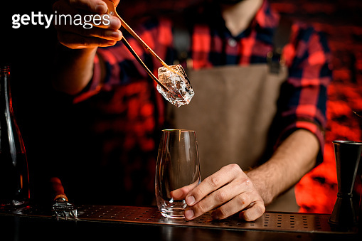 Male bartender put to glass large piece of ice