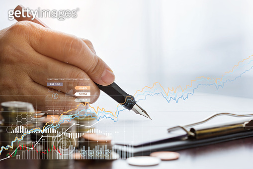 A businessman with a pen is writing finance data and sales on report clipboard paper, along with a growing graph of business.